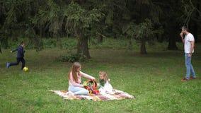 De gelukkige de de de familievader, moeder, zoon en dochter worden gespeeld in het de herfstpark Langzame Motie 4K stock video