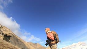 De gelukkige fotograaf van het reizigersmeisje in zonnebril met een camera en een rugzak gaat bergop op een achtergrond van snow- stock video