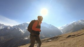 De gelukkige fotograaf van het reizigersmeisje in zonnebril met een camera en een rugzak gaat bergop op een achtergrond van snow- stock footage
