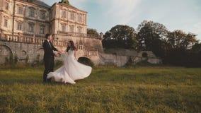 De de gelukkige gangen en roezen van het huwelijkspaar op mooie aard bij kasteel stock footage