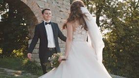 De gelukkige gangen van het huwelijkspaar bij kasteel met glimlachen op gezichten langzaam stock footage