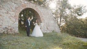 De gelukkige gangen van het huwelijkspaar bij kasteel met glimlachen op gezichten langzaam stock videobeelden