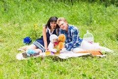 De gelukkige Gemengde Familie die van het Ras een Picknick hebben en in het Park spelen Stock Foto's