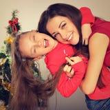 De gelukkige genietende van toothy glimlachende moeder omhelst haar leuke dochter in de hoed van de Kerstman op achtergrond van d stock foto