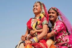 De gelukkige gezichten van dorpsvrouwen in rode kleding drijven de kameel Stock Foto's
