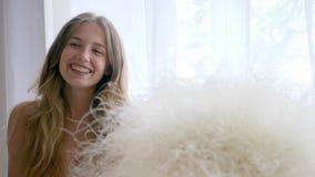 De gelukkige gezonde dame vrij van allergieën met boeket van veergrassen kijkt dichtbij venster in camera stock videobeelden