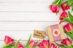 De de gelukkige gift en markering van de Moedersdag met hoekgrens van roze bloemen tegen een witte houten achtergrond royalty-vrije stock foto's