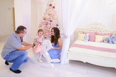 De gelukkige giften van de familieuitwisseling in ruim slaapkamerlicht op backgro Royalty-vrije Stock Afbeeldingen