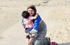 De gelukkige glimlachende Arabische moslimmoeder koestert haar babymeisje Stock Afbeeldingen