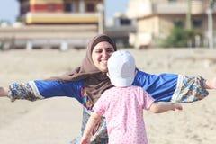 De gelukkige glimlachende Arabische moslimmoeder koestert haar babymeisje Stock Foto