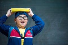 De gelukkige glimlachende Aziatische jongen in glazen gaat naar school stock fotografie