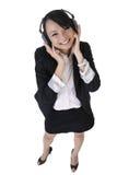 De gelukkige glimlachende bedrijfsvrouw luistert muziek stock afbeeldingen