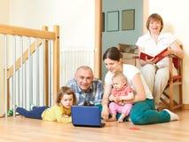 De gelukkige glimlachende familie geniet van op vloer met laptop in woonkamer stock foto's