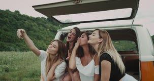 De gelukkige glimlachende jonge dames hebben een grote tijd die samen, selfies zitting op de rug van een retro bestelwagen in het stock video