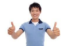De gelukkige glimlachende jonge mens toont duim Stock Afbeeldingen