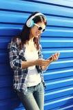 De gelukkige glimlachende jonge vrouw luistert aan muziek in hoofdtelefoons en het gebruiken van smartphone Royalty-vrije Stock Afbeeldingen
