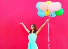 De gelukkige glimlachende jonge vrouw met een lucht kleurrijke ballons heeft pret in de zomer over een roze achtergrond Royalty-vrije Stock Fotografie
