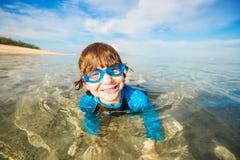 De gelukkige glimlachende jongen met beschermende brillen zwemt in ondiep stock afbeeldingen