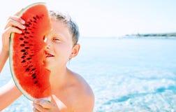 De gelukkige glimlachende jongen met groot watermeloensegment zit dichtbij het overzees stock foto's