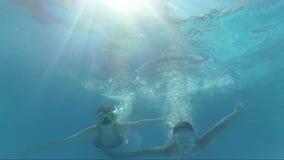 De gelukkige glimlachende meisjes duiken in zwembad, onderwaterspruit, die pret hebben stock footage