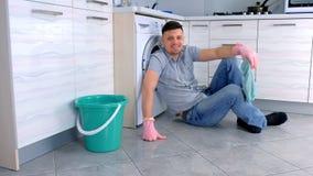 De gelukkige glimlachende mens in rubberhandschoenen heeft een rust van het schoonmaken zitting op de keukenvloer stock videobeelden