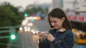 De gelukkige, glimlachende mooie vrouw gebruikt een smartphone zich bevindt op de brug De wind blaast haar haar 4K stock videobeelden