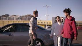 De gelukkige, glimlachende multi-etnische jongeren gaat van de auto en het lopen door streek dichtbij de wandelgalerijen weg rond stock footage
