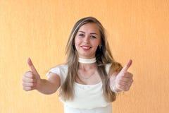 De gelukkige glimlachende vrouw die duimen tonen zucht omhoog Stock Foto's