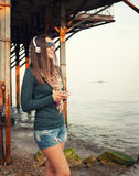 De gelukkige glimlachende vrouw geniet het luisteren van muziek met cameraphone tegen oude pijler royalty-vrije stock afbeeldingen