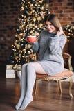 De gelukkige glimlachende vrouw in de sweater drinkt hete chocolade dichtbij de glanzende Kerstmisboom bij haar woonkamer, Kerstm royalty-vrije stock afbeelding