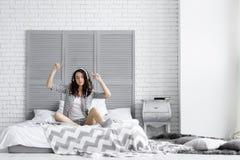 De gelukkige grappige donkerbruine vrouw draagt pyjama's luisterend aan muziek stock fotografie