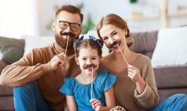 De gelukkige grappige vader van de familiemoeder en kinddochter met snor op stok stock afbeeldingen