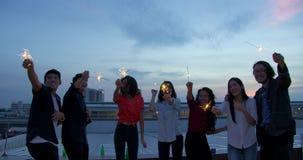 De gelukkige groep jonge vrienden geniet en speelt van sterretje bij dak hoogste partij bij avondzonsondergang Feestelijke vakant stock footage