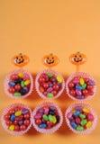 De gelukkige Halloween-truc of behandelt suikergoed op heldere kleurrijke moderne oranje achtergrond Stock Afbeelding