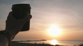 De gelukkige hand die van de reizigersmens zwarte document kop van koffie houden die aan de zonsondergang en het plaatsen zon op  stock footage
