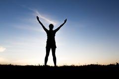 De gelukkige hand van de silhouetvrouw hoog bij zonsondergang royalty-vrije stock fotografie