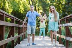 De gelukkige handen van de familieholding met dochter op brug stock fotografie