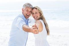 De gelukkige handen van de paarholding en het glimlachen bij camera Royalty-vrije Stock Fotografie