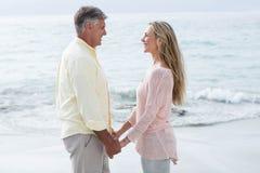 De gelukkige handen van de paarholding en het glimlachen bij elkaar Royalty-vrije Stock Fotografie