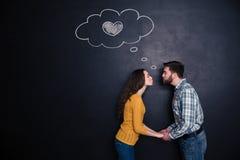 De gelukkige handen van de paarholding en het kussen over rugplankachtergrond Royalty-vrije Stock Afbeeldingen