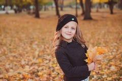 De gelukkige Herfst Een klein meisje in een rode baret speelt met dalende bladeren en het lachen royalty-vrije stock afbeeldingen