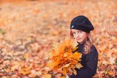 De gelukkige Herfst Een klein meisje in een rode baret speelt met dalende bladeren en het lachen royalty-vrije stock foto