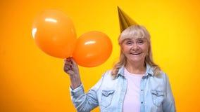 De gelukkige het glimlachen bejaarde ballons van de dameholding op gele achtergrond, verjaardag stock afbeeldingen