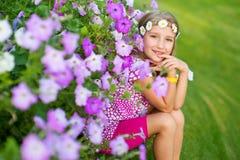 De gelukkige het glimlachen blonde modelzitting van het kindmeisje op gras in bloemen Stock Afbeelding