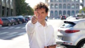 De gelukkige het glimlachen tablet van de bedrijfsmensenholding in langzame motie van het straat de o.k. teken stock video