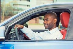 De gelukkige het glimlachen zitting van de jonge mensenkoper in zijn nieuwe auto Stock Foto's