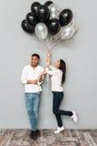 De gelukkige het houden van ballons van de paarholding Royalty-vrije Stock Afbeelding