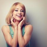 De gelukkige het lachen blonde jonge hand van de vrouwenholding bij gezicht Gestemd CLO Royalty-vrije Stock Foto's
