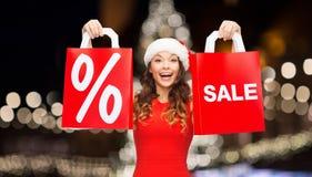 De gelukkige hoed van vrouweninsanta met het winkelen zakken Royalty-vrije Stock Foto's