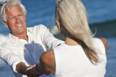 De gelukkige Hogere Handen van de Holding van het Paar op een Strand Royalty-vrije Stock Afbeeldingen